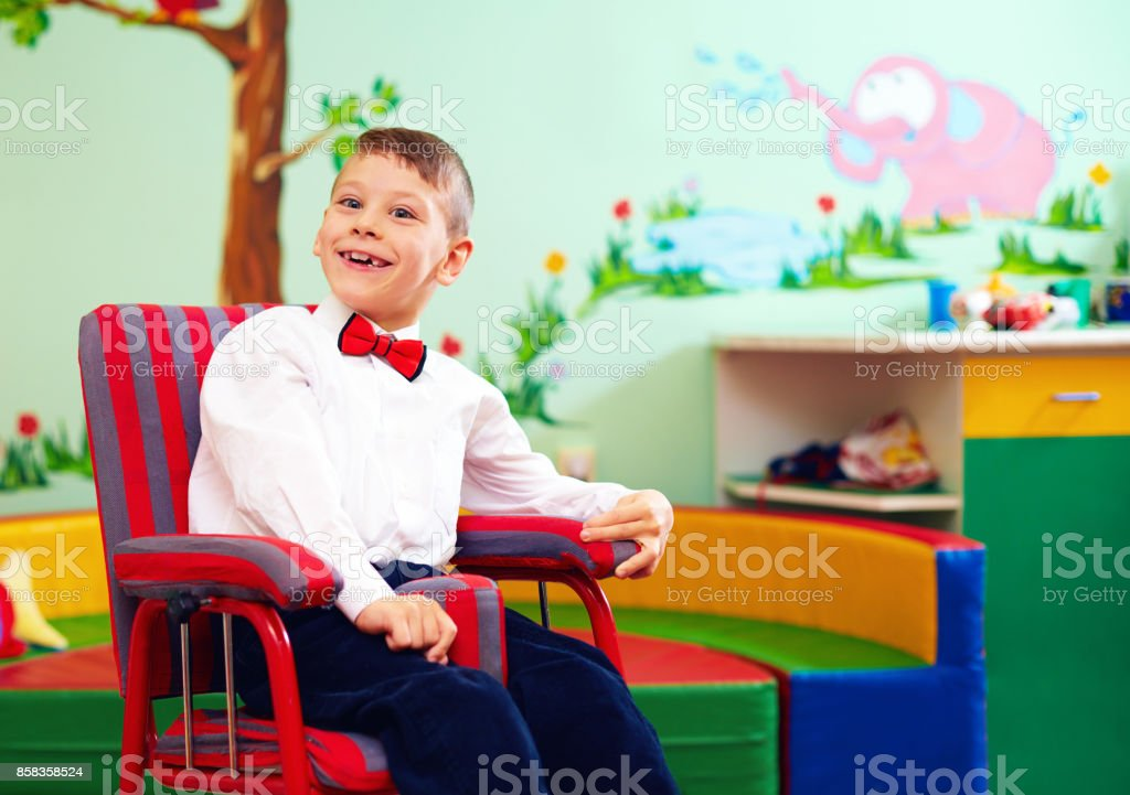 cute happy kid in wheelchair, wearing glad rags in center for children with special needs - foto stock