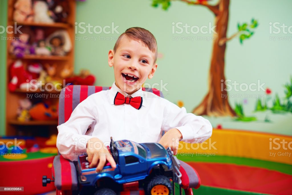 cute happy kid on wheelchair with present in kindergarten for kids with special needs - foto stock