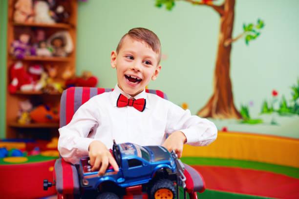 niedliche glückliches kind im rollstuhl mit geschenk im kindergarten für kinder mit besonderen bedürfnissen - besondere geschenke stock-fotos und bilder