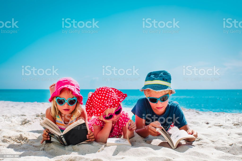 cute happy kids -boy and girls- read books on beach, family vacation cute happy kids -boy and girls- read books on beach, family vacation concept 2-3 Years Stock Photo