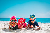 cute happy kids -boy and girls- read books on beach, family vacation concept