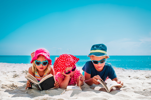 Cute Happy Kids Boy And Girls Read Books On Beach Family Vacation Stock Photo - Download Image Now