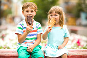 Cute happy kids eating icecream outdoors. childhood concept.