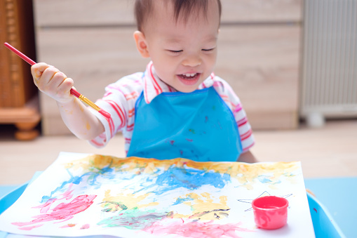 1042756824 istock photo Cute happy little Asian 18 months / 1 year old toddler boy child painting with paint brush and watercolors 938645196