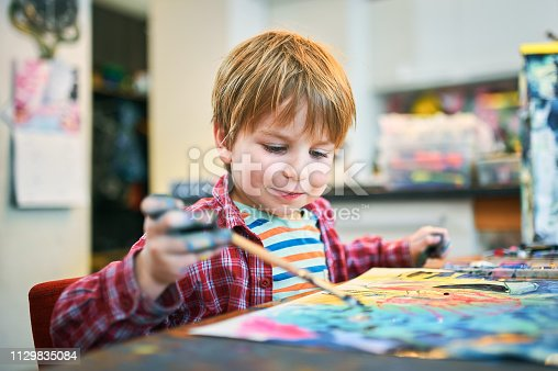 istock Cute happy little boy, adorable preschooler, painting in a sunny art studio. Young artist at work 1129835084