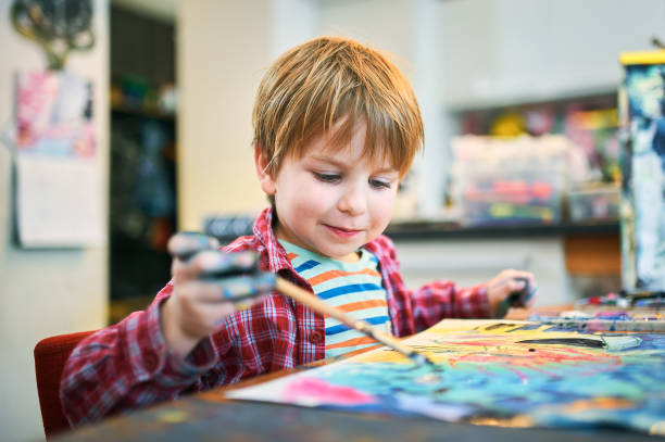 Cute happy little boy, adorable preschooler, painting in a sunny art studio. Young artist at work stock photo