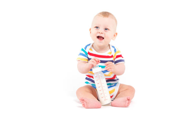 cute happy little boy in colorful shirt with milk stock photo