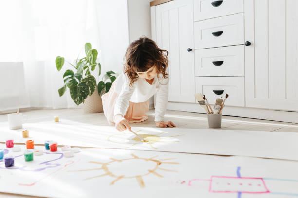 Süße glückliche kleine Mädchen, entzückende Vorschulkind, Malerei mit Farben auf Papierrolle – Foto