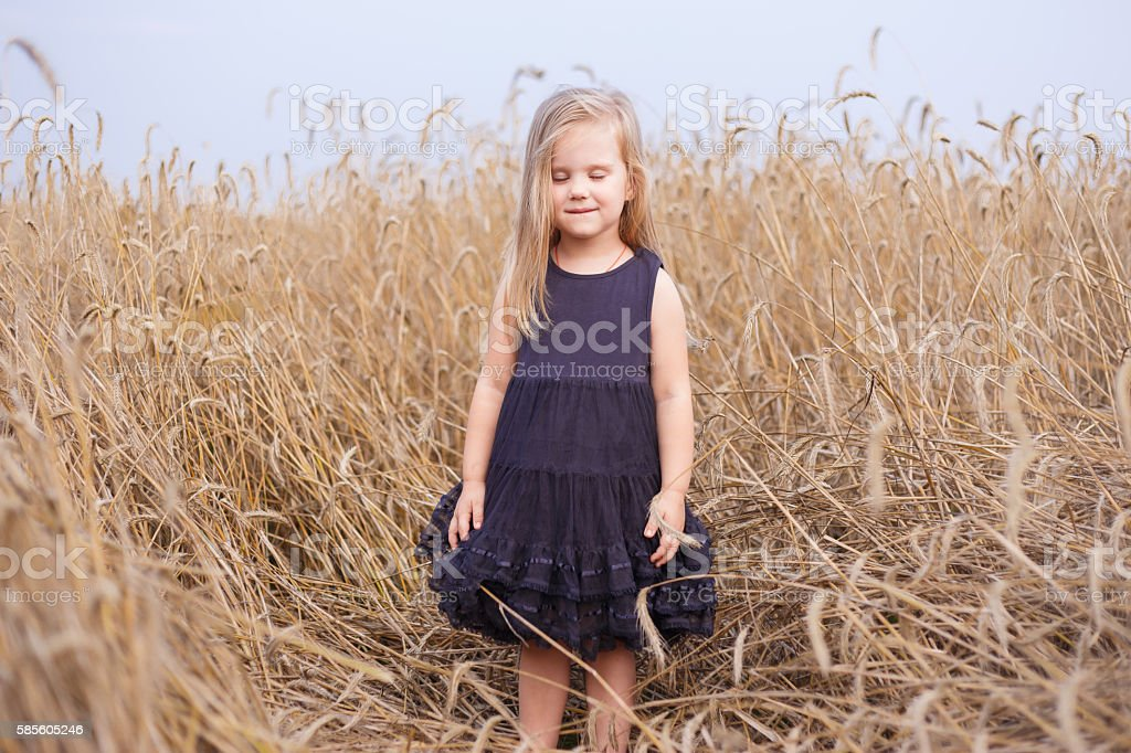 Cute happy little girl dreams in wheat field and listens stock photo