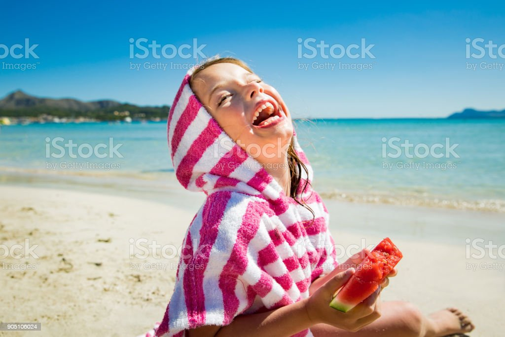 Cute happy little girl eating watermelon stock photo