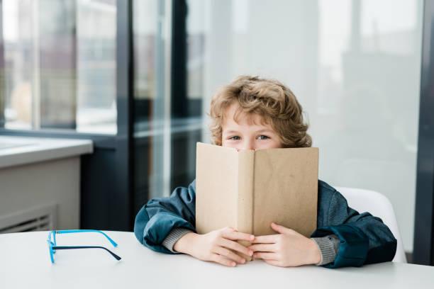 Nette glückliche kleine Schuljunge guckt aus offenem Buch bei Lektion der Literatur – Foto