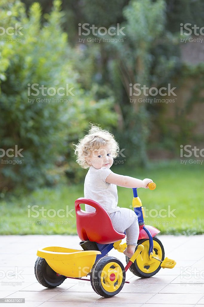 Cute happy smiling baby girl riding her first bicycle stock photo