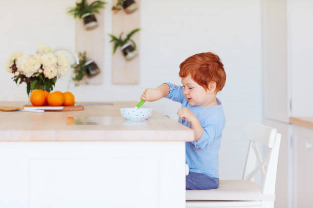 cute happy toddler baby boy sitting at the table, having breakfast in the morning stock photo