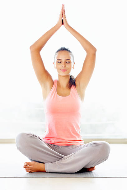 Cute happy woman meditating with hands joined over head Cute smiling woman meditating with hands joined over head lotus position stock pictures, royalty-free photos & images