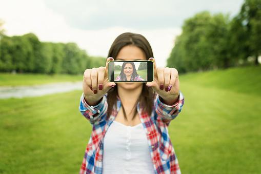 Cute happy woman taking a selfie photo outdoors