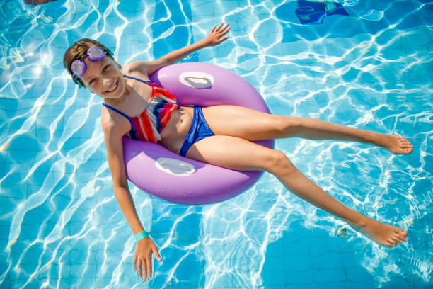 cute happy young girl relaxing in swimming pool - girl alone in swimsuit stock photos and pictures
