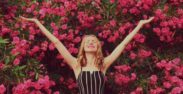 Cute happy young woman raising her hands up on a pink roses flowers background stock photo