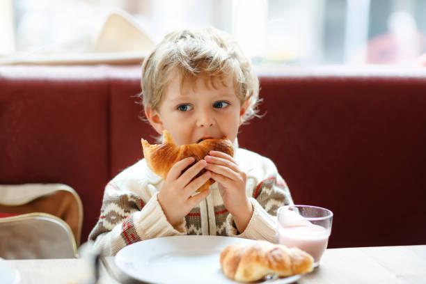 Niedlicher gesunder Junge, der Croissant isst und Erdbeermilchshake im Café trinkt. Ein gutes Kind, das mit den Eltern oder im Kindergarten frühstücken muss. Gemüse, Eier als gesundes Essen für Kinder. – Foto