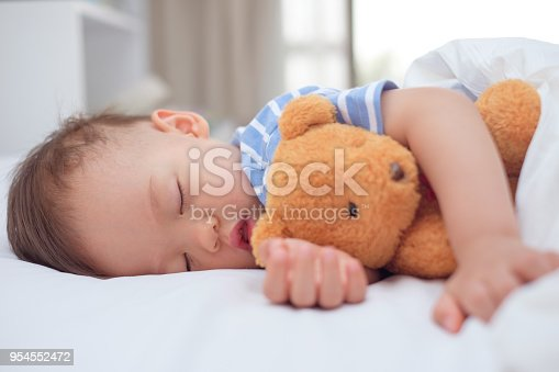 istock Cute healthy little Asian toddler baby boy child sleeping / taking a nap under blanket in bed while hugging teddy bear 954552472