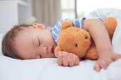 Cute healthy little Asian 18 months / 1 year old toddler baby boy child sleeping / taking a nap under blanket in bed while hugging teddy bear, Daytime sleep, kid deep sleeping, sweet dream concept