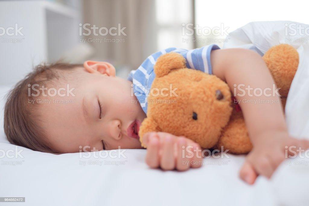 Süße gesunde asiatische Kleinkind Baby junge Kindlein schlafen / ein Nickerchen unter Decke im Bett während umarmt Teddybär – Foto