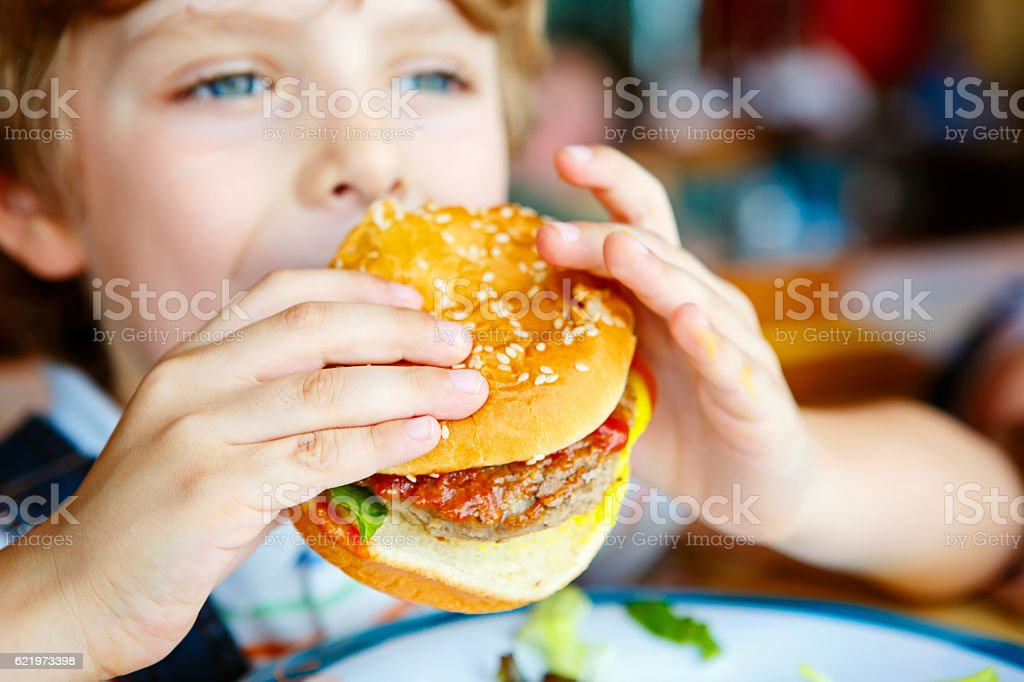 Cute healthy preschool boy eats hamburger sitting in cafe outdoo stock photo