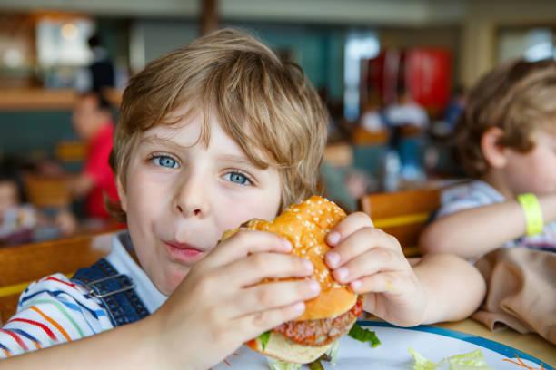 bonito rapaz prées-escolar saudável come hambúrguer sentado na cantina da escola - junk food - fotografias e filmes do acervo