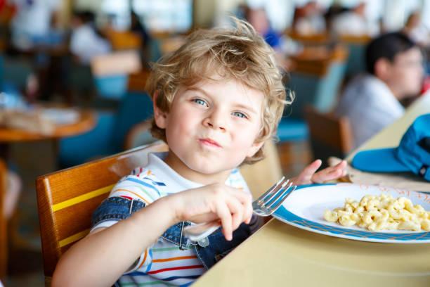 süße gesunde vorschule junge isst nudeln sitzen in schulküche - schulkind nur jungen stock-fotos und bilder