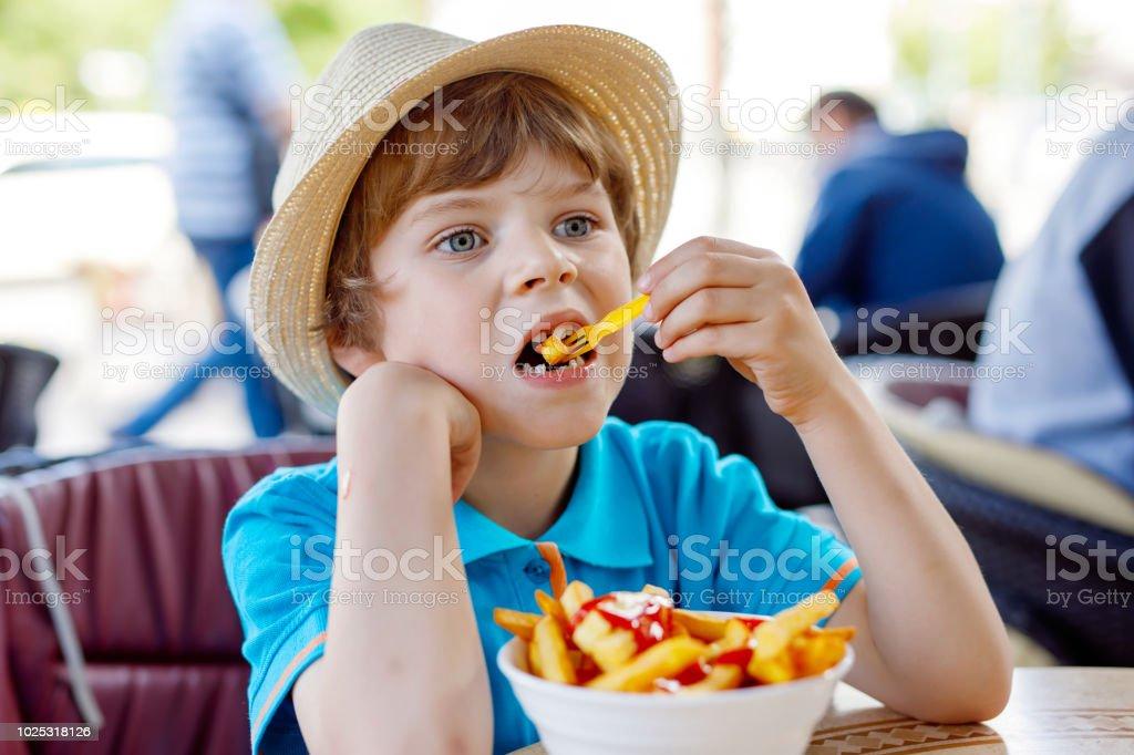 Süße gesunde Vorschule Kind junge isst Kartoffeln Pommes Frites mit ketchup – Foto