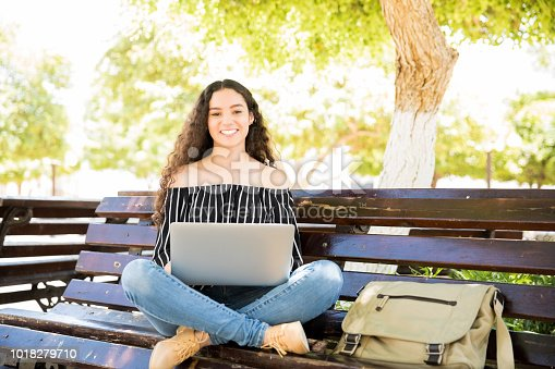 istock Cute high school girl with laptop on park bench 1018279710