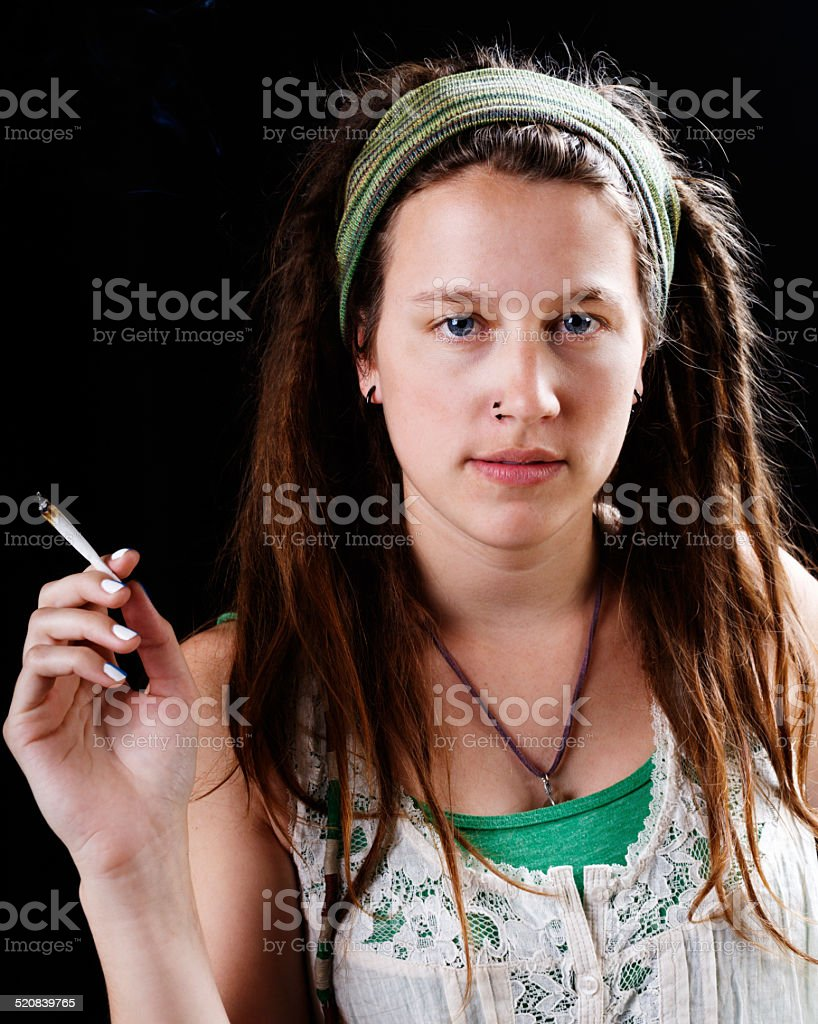 Cute hippie with dreadlocks and marijuana smiles gently. Life's cool. stock photo