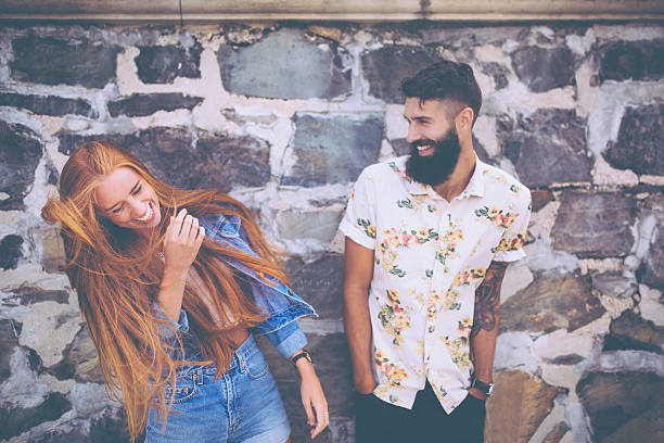 cute hipster couple laughing in front of a stone wall - styles stock photos and pictures