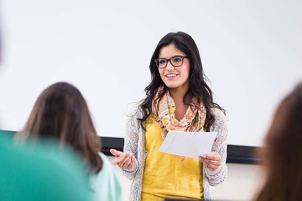 Cute hipster student reading report in front of classmates stock photo