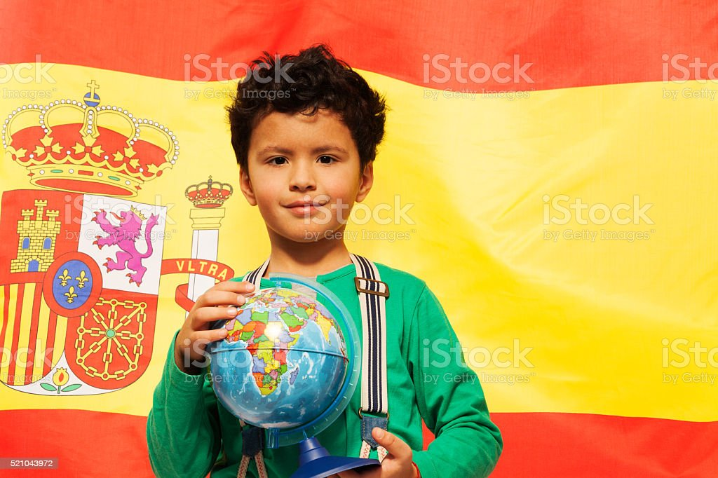 Cute Hispanic boy learn geography with globe stock photo