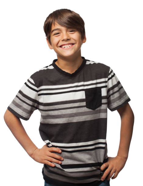 Cute hispanic boy smiling at camera with hands on waist stock photo