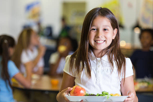 hübsch hispanic grundschule schüler hält teller mit cafeteria speisen - kantine stock-fotos und bilder