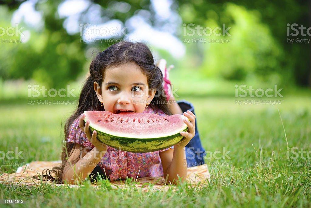 Cute hispanic girl eating watermelon stock photo