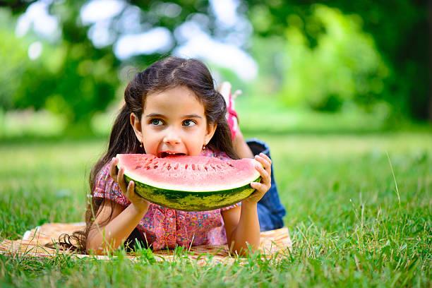 süße hispanischen mädchen isst wassermelone - mensch isst gras stock-fotos und bilder