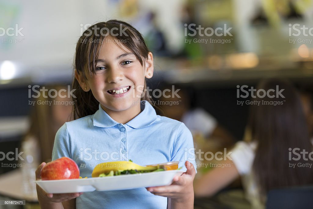 Cute Hispanic girl in private school cafeteria lunchroom stock photo