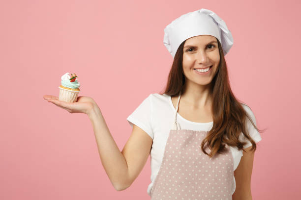 Cute housewife chef cook confectioner baker in white t-shirt, toque chefs hat cooking hold sweet isolated on pink pastel background in studio. Cupcake making process. Mock up copy space food concept. stock photo