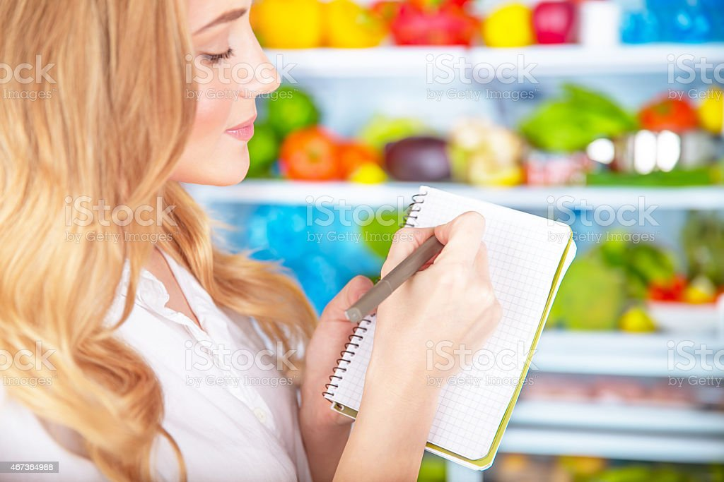Cute housewife writing list to supermarket stock photo