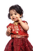 Cute Indian baby girl with traditional Indian dress on white.