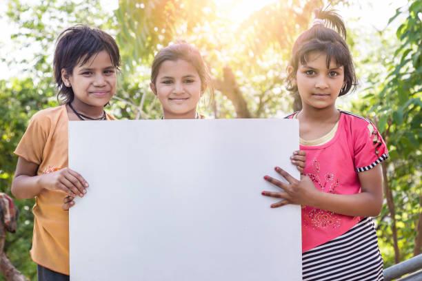 3 niedliche indische mädchen mit plakat, leeres schild, im freien - sprüche kinderlachen stock-fotos und bilder