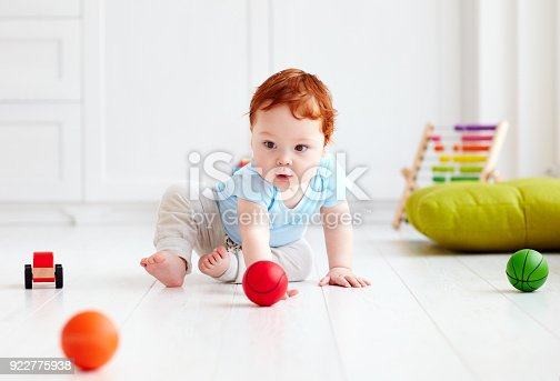istock cute infant baby crawling on the floor at home, playing with colorful balls 922775938