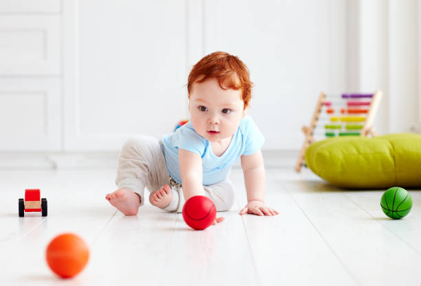 cute infant baby crawling on the floor at home, playing with colorful balls stock photo