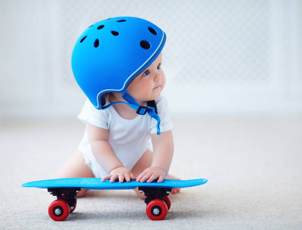 cute infant baby girl in protective helmet outfit ready to ride skateboard, extreme sport concept stock photo