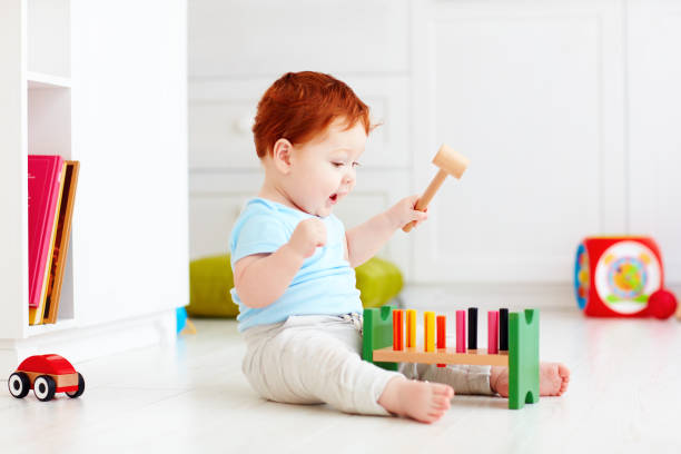 cute infant baby playing with wooden hammer block toy stock photo