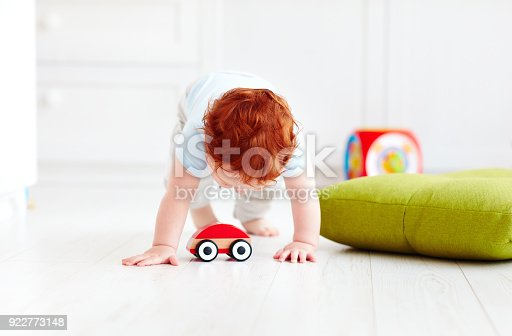 184659330 istock photo cute infant baby playing with wooden toy car at home 922773148
