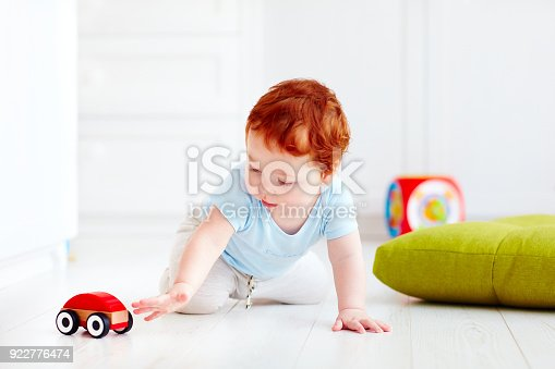 184659330 istock photo cute infant baby playing with wooden toy car at home 922776474