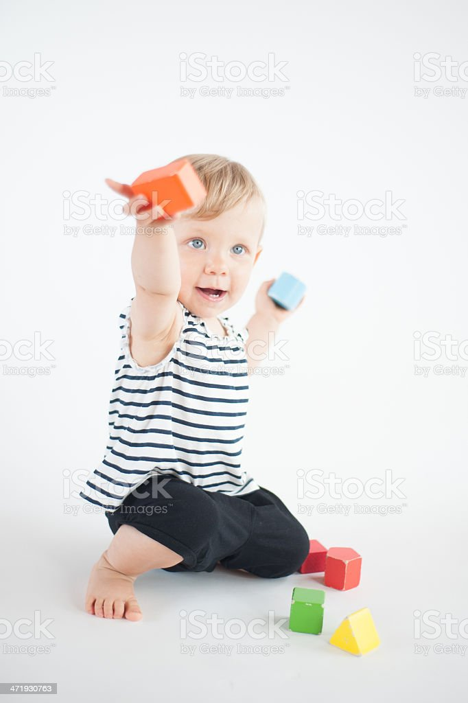 e256ce1b3 Cute infant girl playing with building bricks on white royalty-free stock  photo